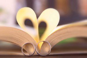 Сватбени халки пред отворена книга.